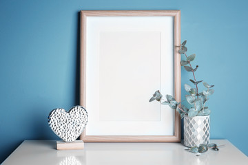 Empty wooden frame, decorative heart statuette and eucalyptus on table near color wall