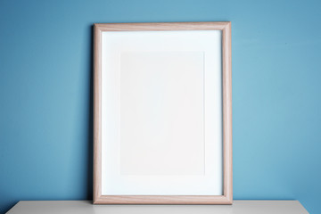 Empty wooden frame on table near color wall