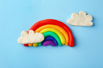 Plasticine rainbow with clouds on color background