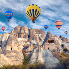 Hot air balloons over unique geological formations in Cappadocia, Central Anatolia, Turkey