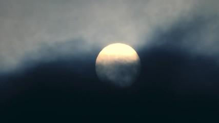 Fotobehang - Sun setting in dark clouds at sunset. 4K UHD timelapse.