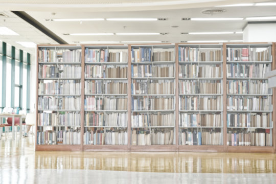 Abstract blurred bookshelf in library room.