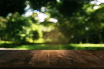 image of wooden table in front of abstract blurred background of outdoor garden lights. can be used for display or montage your products.Mock up for display of product