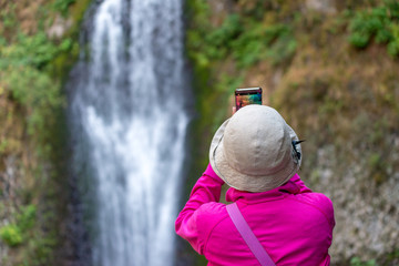 Tourist taking a picture of waterfalls