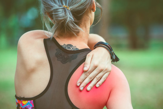 Woman holding her shoulder and back with red painful. Pain relief concept