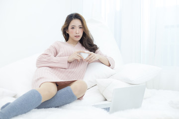 Asian Woman holding coffee cup at bedroom. Attractive female using laptop at bedroom. People lifestyle concept.