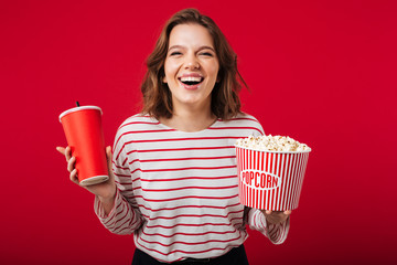 Portrait of a laughing woman holding popcorn