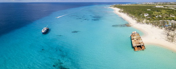 Wall Mural - Aerial panorama of Grand Turk with clear water, boats, and shipwreck.