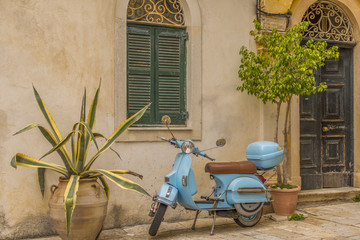 Fototapeten Scooter Corfu, Greece- December 21, 2017: Narrow streets and alleys in Corfu town Greece.Architecture in the old town of Corfu is heavily influenced my the Venetian architecture.Blue Vespa outside a building.