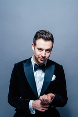 Portrait of a young handsome man in a suit, seriously looking at the camera, dramatic lighting, against plain studio background
