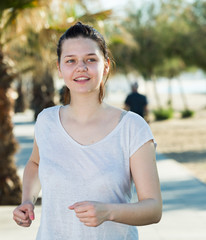 Female 20-30 years old is jogging in white T-shirt