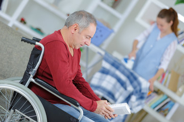 man on wheelchair and nurse helping with ironing