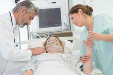 doctors examine female patient in hospital