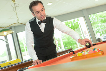 man playing billiards and smiling in billiard club