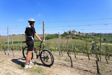 Man with mountain bike on vineyards, Langhe, Italy