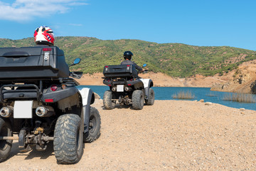 Two mans in protective helmets is driving ATV on off-road.