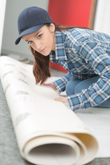 female worker unrolling carpet
