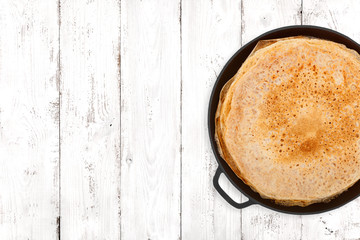 Crepes in a cast iron pan on light wooden background, top view