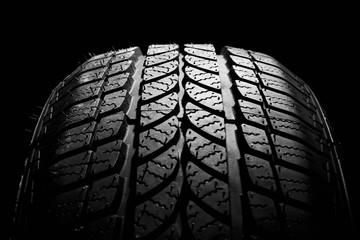 car winter tyre on black  background. vehicle wheel pneumatic