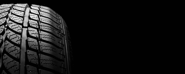 car winter tyre on black  background. vehicle wheel pneumatic