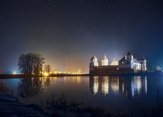 Landscape of Mir Castle in starry night. clear night sky on Mirsky Castle with reflections in lake and city's shining in background, Belarus.