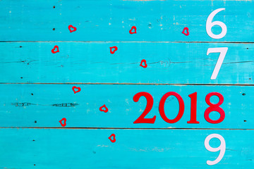 Year 2018 between 2016, 2017, and 2019 with red hearts on antique teal blue wood background; holiday sign with copy space