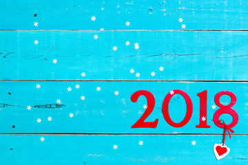 Year 2018 in bold red with heart hanging on snow covered antique teal blue rustic background; blank holiday sign