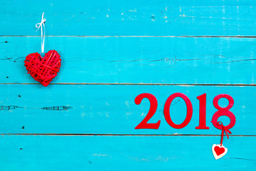 Year 2018 in bold red with hearts hanging on antique rustic teal blue background; blank holiday sign