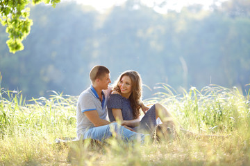 Romance and love. Dating and park. Loving couple sitting together on grass near the lake
