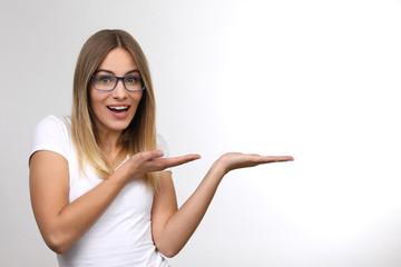 Hübsche blonde Frau mit Brille lacht und zeigt in eine Richtung