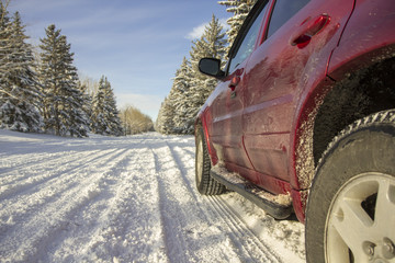 Colse up of the side of a red SUV on a snowy road, alley