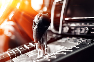 Close-up on automatic transmission lever in modern car. multimedia and navigation control buttons. Car interior details. Transmission shift.