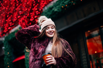 Portrait pretty girl with long hair in Burgundy fur coat of artificial fur knitted hat and bright burgundy lips walking on street with coffee to go. She looks excited to camera City lifestyle