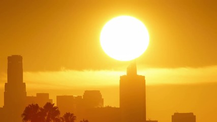 Fototapete - Sunrise sun rising above downtown Los Angeles city skyline. 4K UHD timelapse.