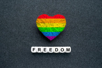 Knitted heart with Lgbt gay rainbow flag and words Freedom on a dark felt background. Multicolored Heart in the gay pride flag. LGBT transgender movement