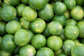 Fresh Juicy Green Tangerine Heap on Market Stall