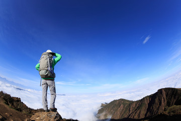 Successful woman backpacker standing on mountain peak cliff edge