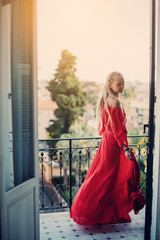 Beautiful female wearing blond dread locks and red dress, resting on balcony, European city