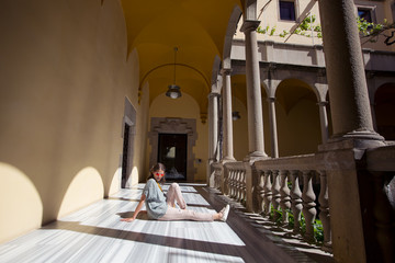 Traveller girl sitting on the floor in European  architecture building, enjoying summer day and and resting