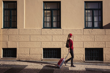 Traveler girl walking in European city with red suitcase