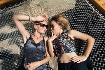 Two happy girls lying in big hammock, enjoying summer day outdoors