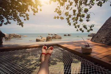 woman leg in hammock, coconut, blue sea, sunny summer day, enjoying and relaxing