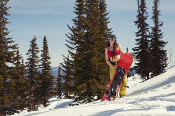 Portrait of happy young snowboarder female with snowboard in winter forest. Sunny holiday, snow sport outdoor, free people
