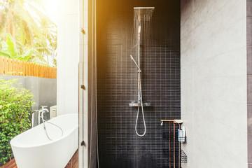 Bathroom in luxury villa interior. Bath outdoor, water coming from shower