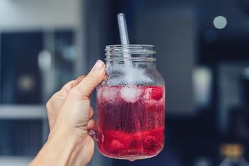 Raspberry water in jar in woman hand