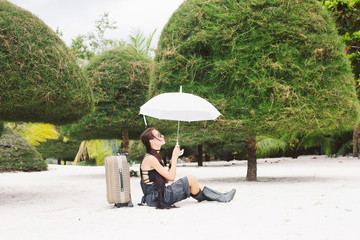 Beautiful style girl with suitcase and umbrella on tropical beach. Rain season in tropic