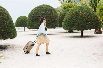 Beautiful style girl walking with suitcase on tropical beach