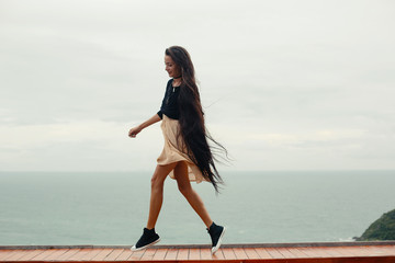 Young female with very long hair have fun and enjoy on sea shore