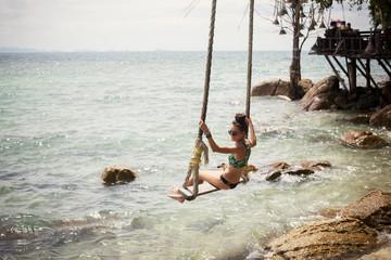 woman on swing at sea shore, tropical holidays