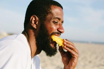 Man with beard and dark skin eating mango on sea shore